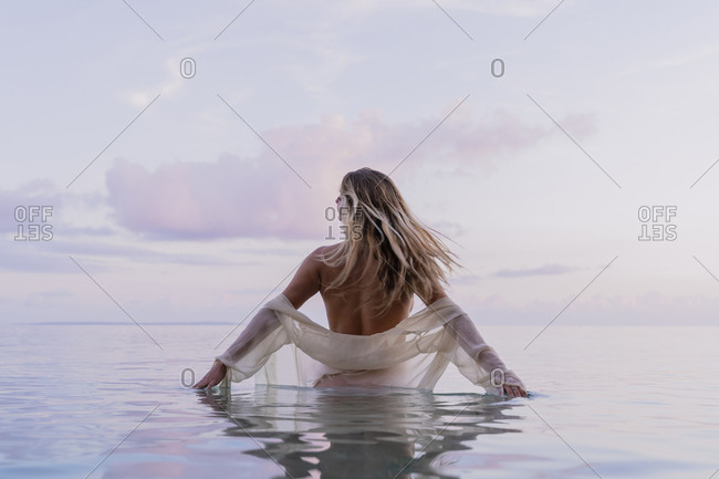Rear view of young woman wearing white blouse inside sea during sunset