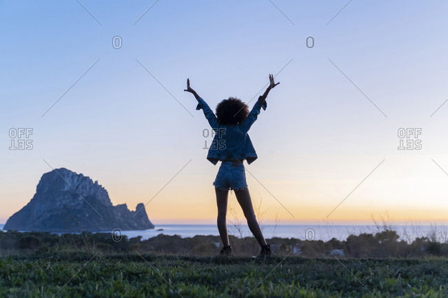 Rear view of young woman standing on a viewpoint with raised arms at sunset- Ibiza