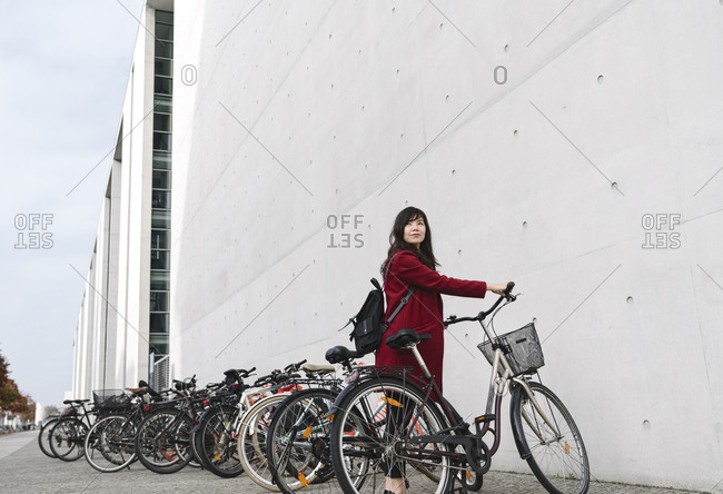 Businesswoman taking bicycle in the background of modern building