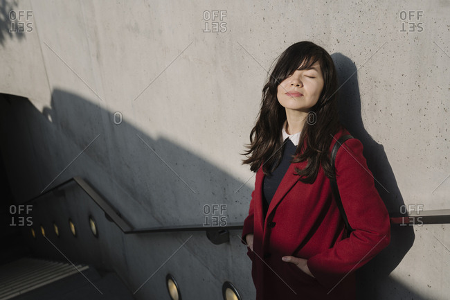 Germany- Berlin- Portrait of businesswoman with closed eyes in the entrance of metro station