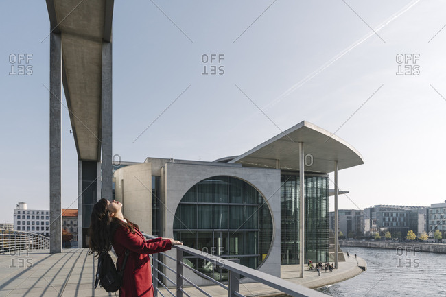 Modern businesswoman getting relaxed in the background of modern buildings- Government District- Berlin-Mitte- Germany