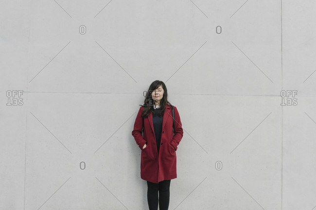 Portrait of modern businesswoman in front of a wall