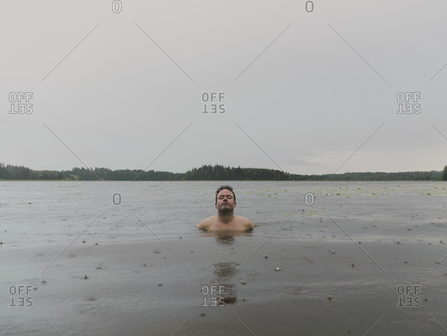 Portrait of a man with eyes closed bathing in lake on rainy day