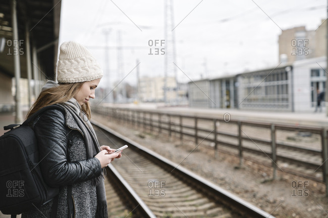 Smiling young woman with backpack standing on platform using cell phone