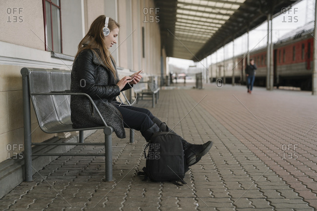 Smiling young woman with backpack sitting on platform using smartphone and headphones- Vilnius- Lithuania