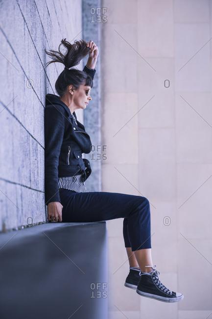 Women with sun glasses sitting on ledge