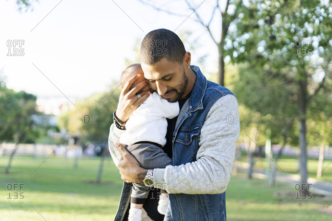 Father carrying his baby son in the park