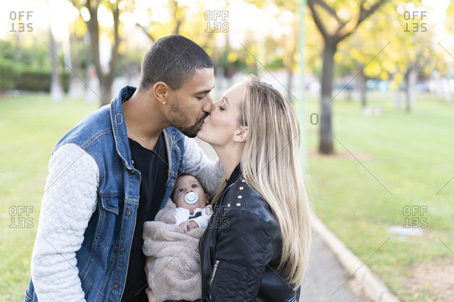Happy parents kissing in park- with baby son between them