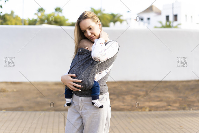 Mother carrying baby boy in sling outdoors
