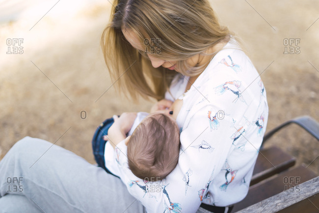 Mother breastfeeding baby boy on a park bench