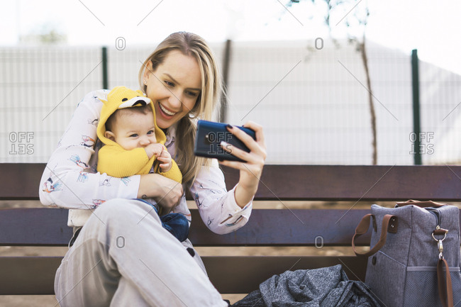 Happy mother resting with baby boy on a park bench taking a selfie