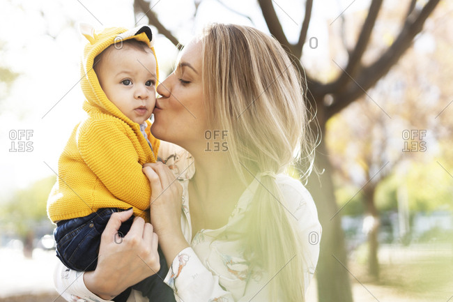 Mother kissing baby boy in a park