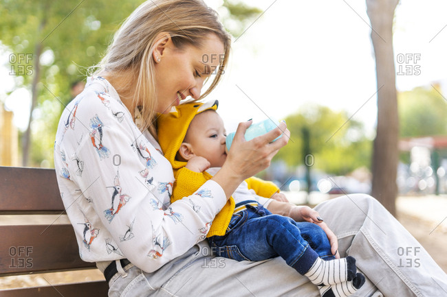 Mother bottle-feeding baby boy on a park bench