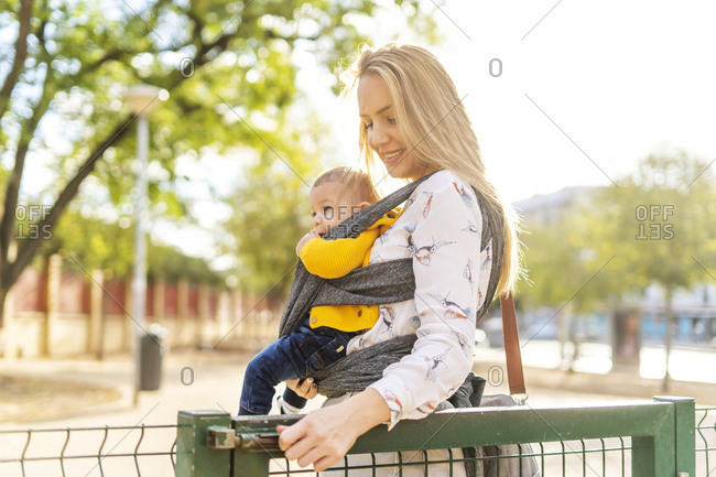 Mother carrying baby boy in a sling opening a gate