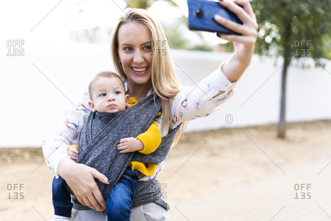 Happy mother with baby boy in a sling taking a selfie