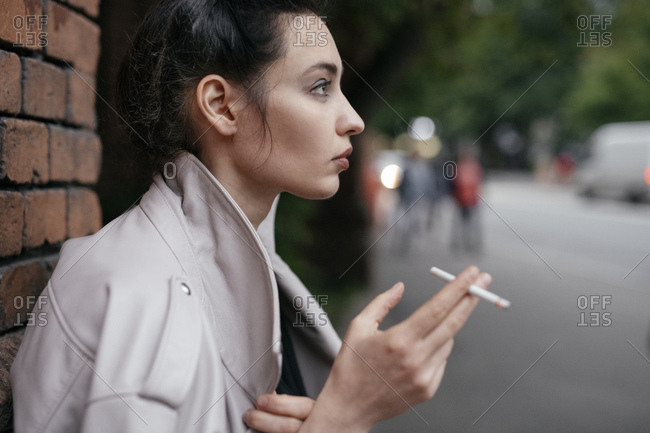Profile of pensive woman with cigarette outdoors
