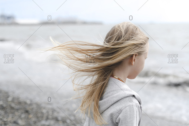 Girl with blowing hair at the seafront