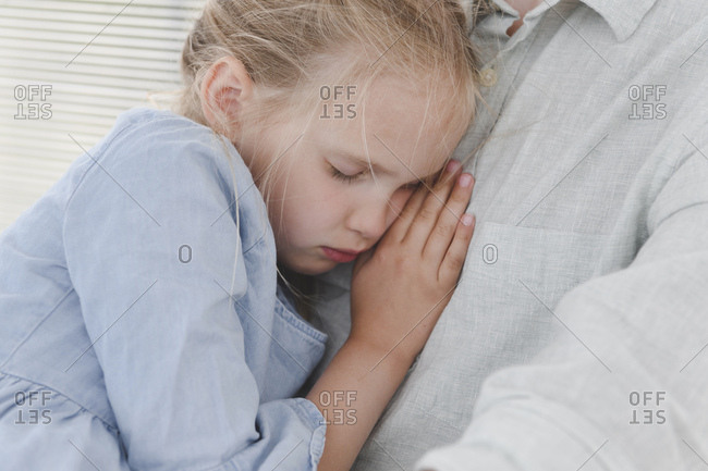 Sleeping girl leaning against father's chest