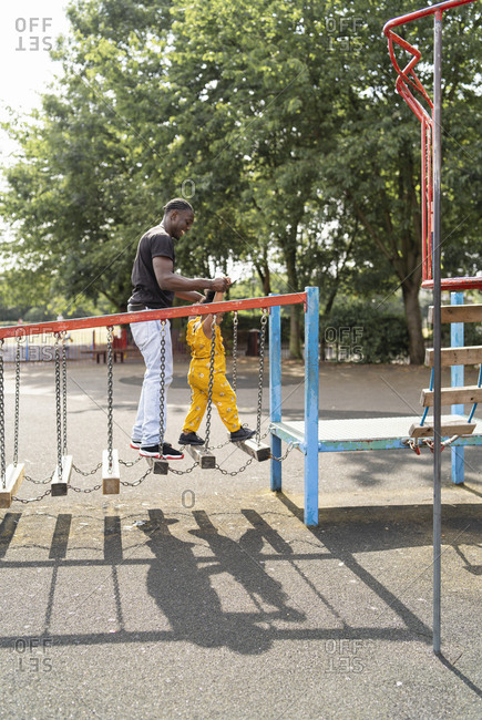 Father and daughter balancing on wooden steps on a playground