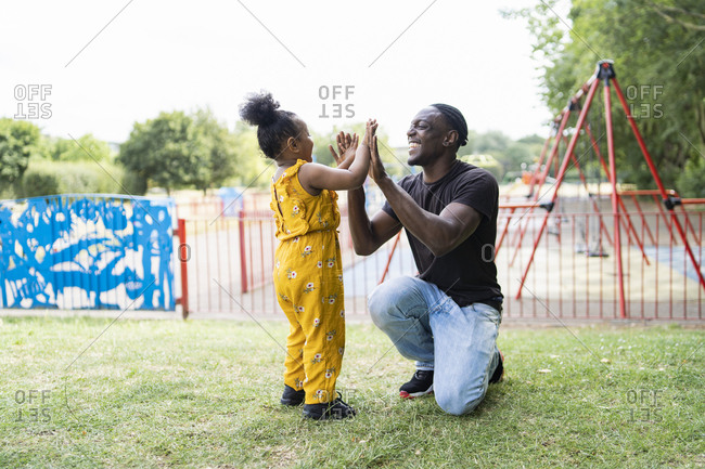 Happy father and daughter playing a clapping game in a park