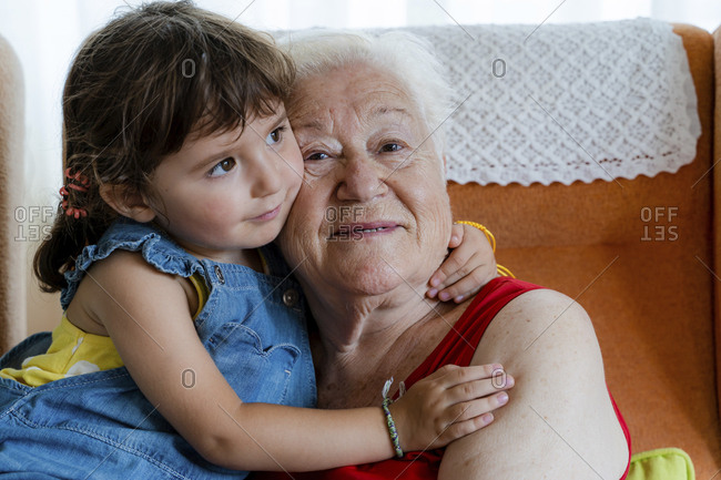 Smiling grandmother hugging her granddaughter at home