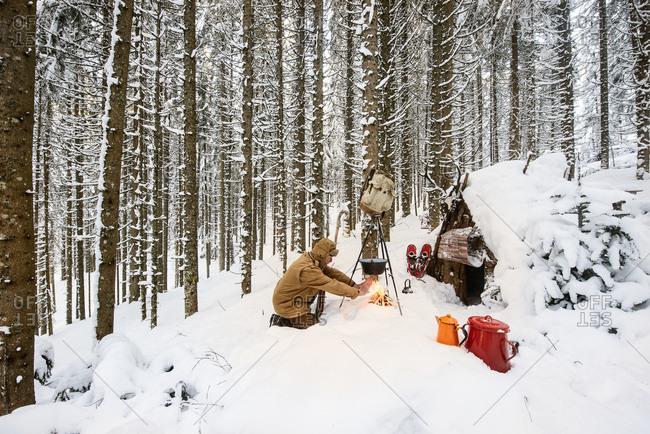 Man preparing tea in winter forest next to a wooden shelter- Salzburg State- Austria