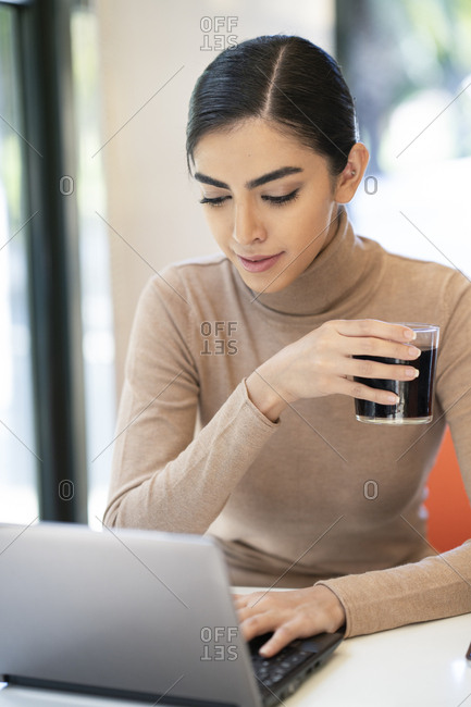 Young woman having a drink and using laptop in a cafe