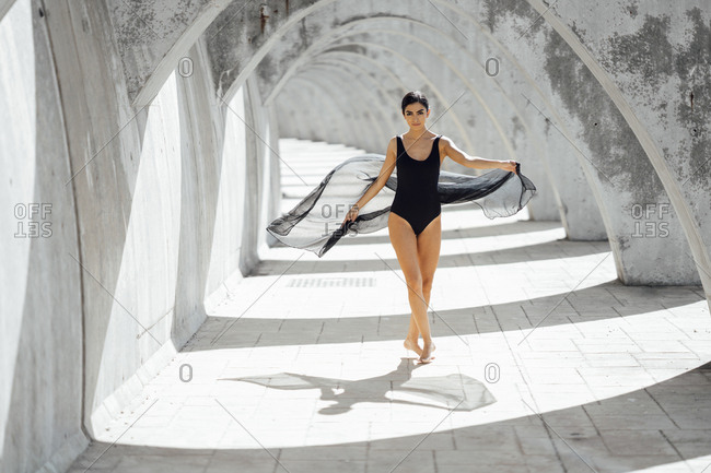 Young woman wearing black swimsuit dancing in an archway