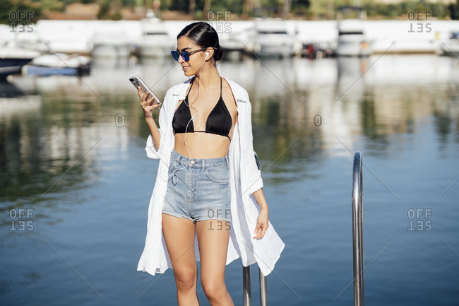 Young woman with earphones and smartphone at the waterfront