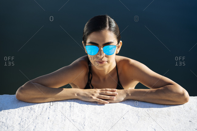 Portrait of young woman wearing sunglasses and bikini leaning on quay wall