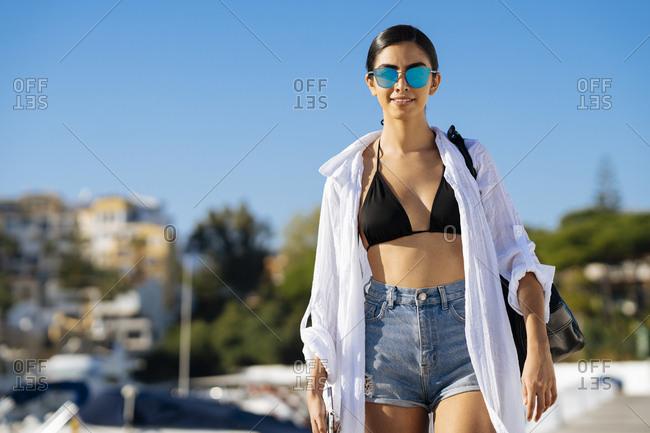 Portrait of young woman walking at a marina
