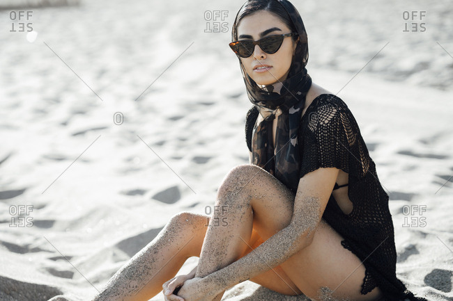 Young woman wearing headscarf and sunglasses sitting on the beach