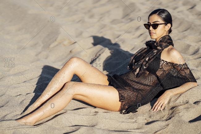 Young woman wearing headscarf and sunglasses lying on the beach