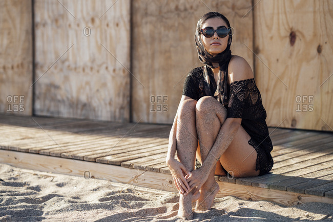 Young woman wearing headscarf and sunglasses sitting at the beach