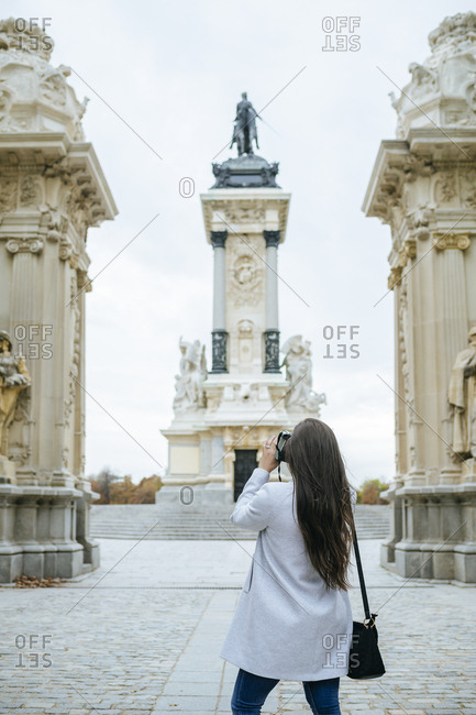 Woman taking a photo of Alfonso XII monument in El Retiro park- Madrid- Spain