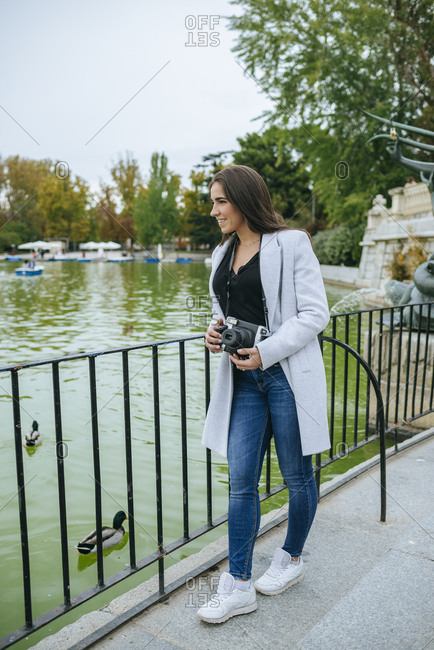 Woman with camera standing at a lake in El Retiro park- Madrid- Spain