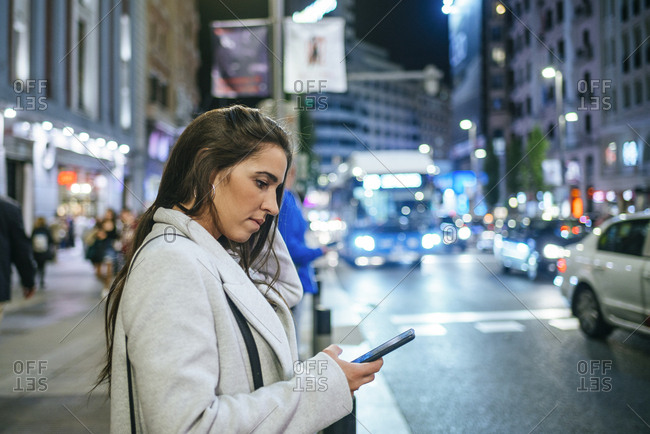 Woman using her smartphone in the street at night