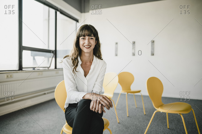 Smiling businesswoman sitting on a chair in an empty office