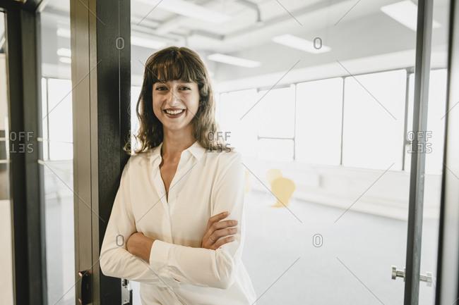 Smiling businesswoman standing in an open office door