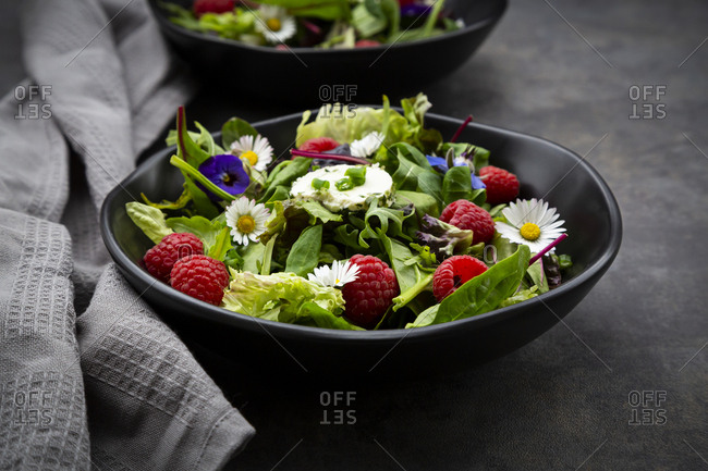Bowl of fresh salad with arugula- spinach- chard- oak leaf-lollo rosso lettuce- corn salad- raspberries- cream cheese- chive and edible flowers