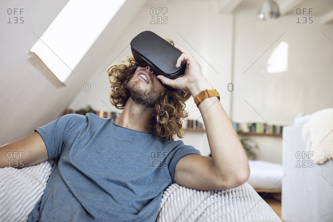 Young man wearing VR glasses at home