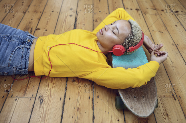 Young woman lying on skateboard on the floor at home listening to music
