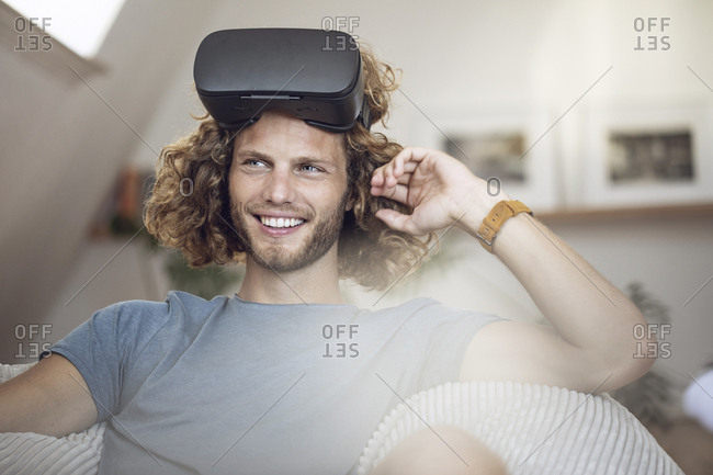 Portrait of smiling young man wearing VR glasses at home