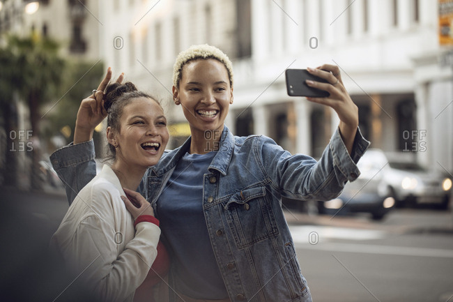 Two carefree young women taking a selfie in the city