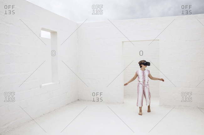 Little girl discovering empty space with VR goggles