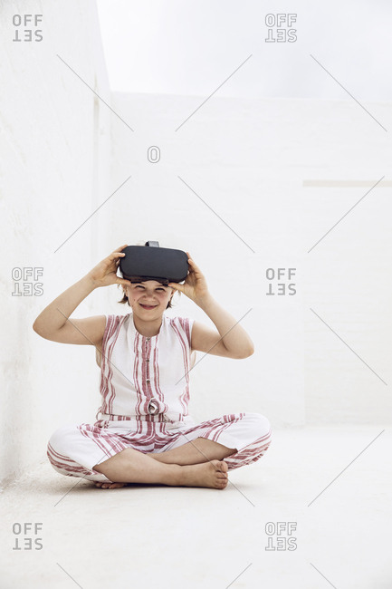 Girl with VR goggles sitting on ground of empty space