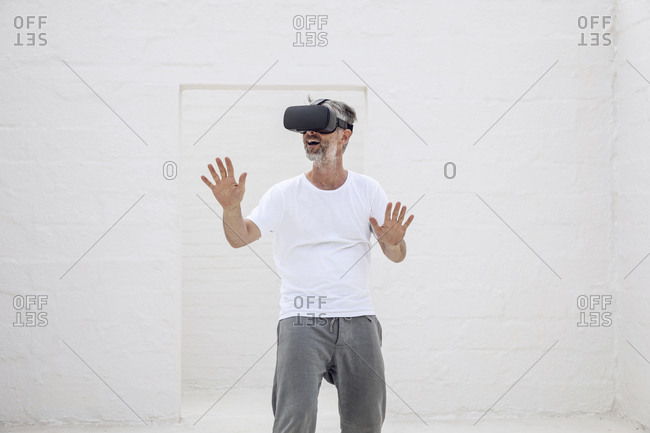 Mature man discovering empty space with VR goggles