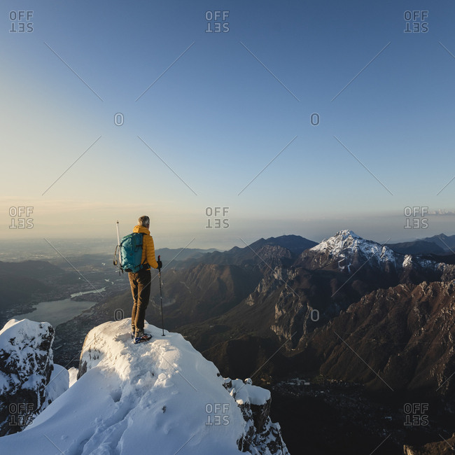 Mountaineer standing on top of a snowy mountain enjoying the view- Lecco- Italy
