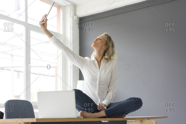 Young businesswoman sitting on desk in office taking a selfie with tablet