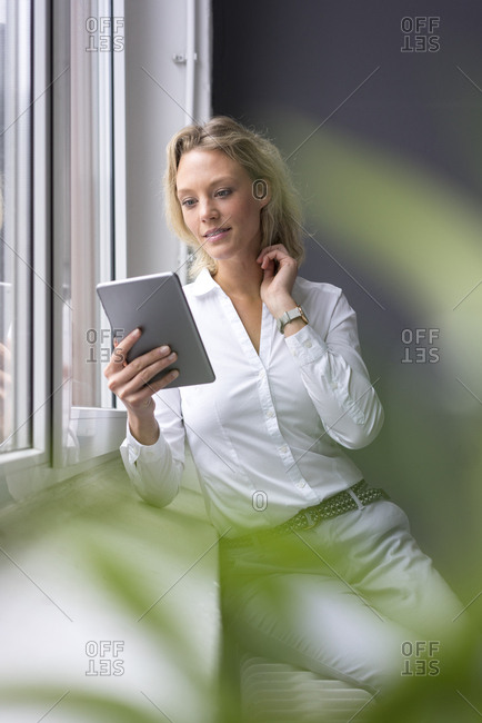 Young businesswoman using tablet at the window